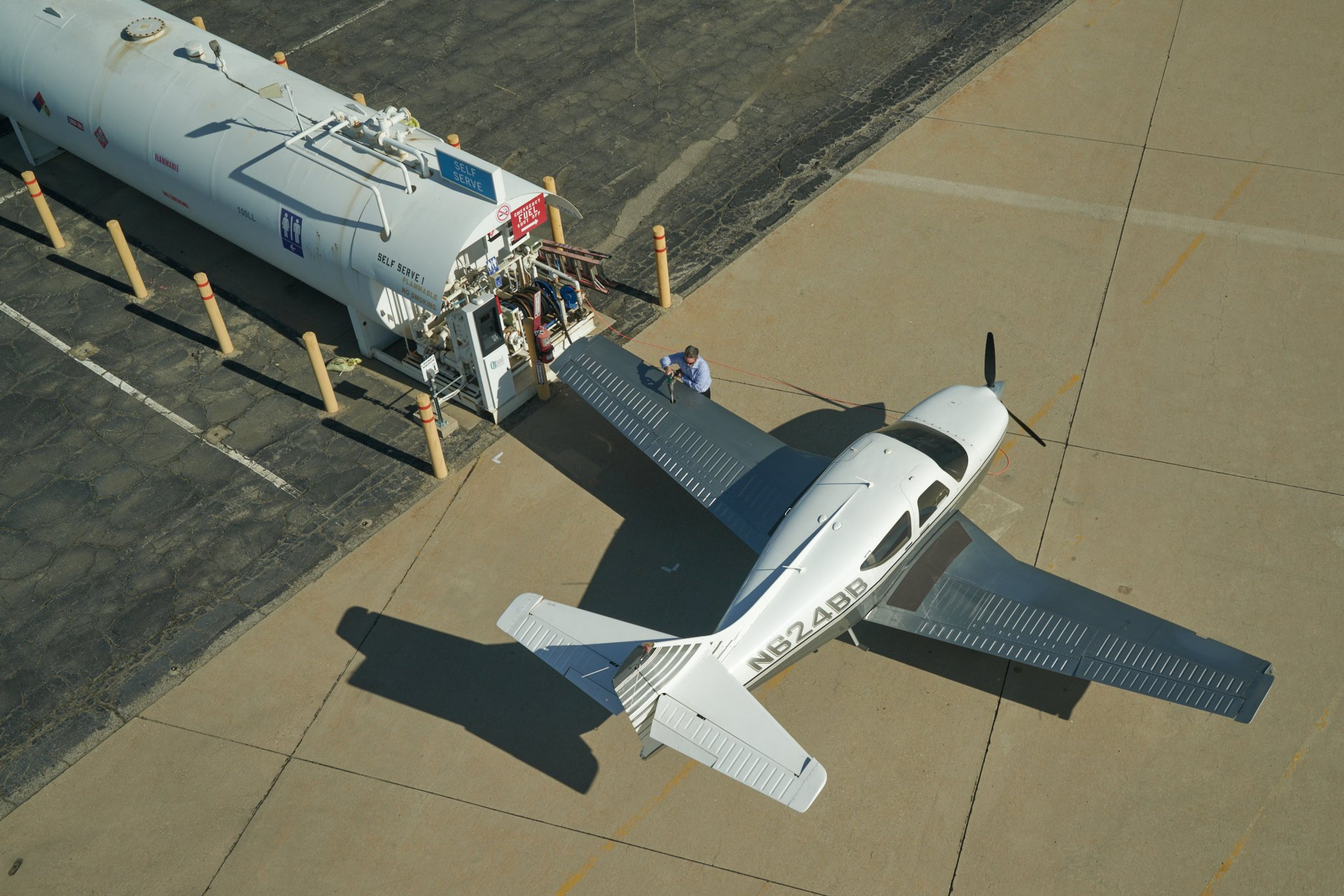 Image of pilot fueling a small single engine plane on the ramp at SBD airport